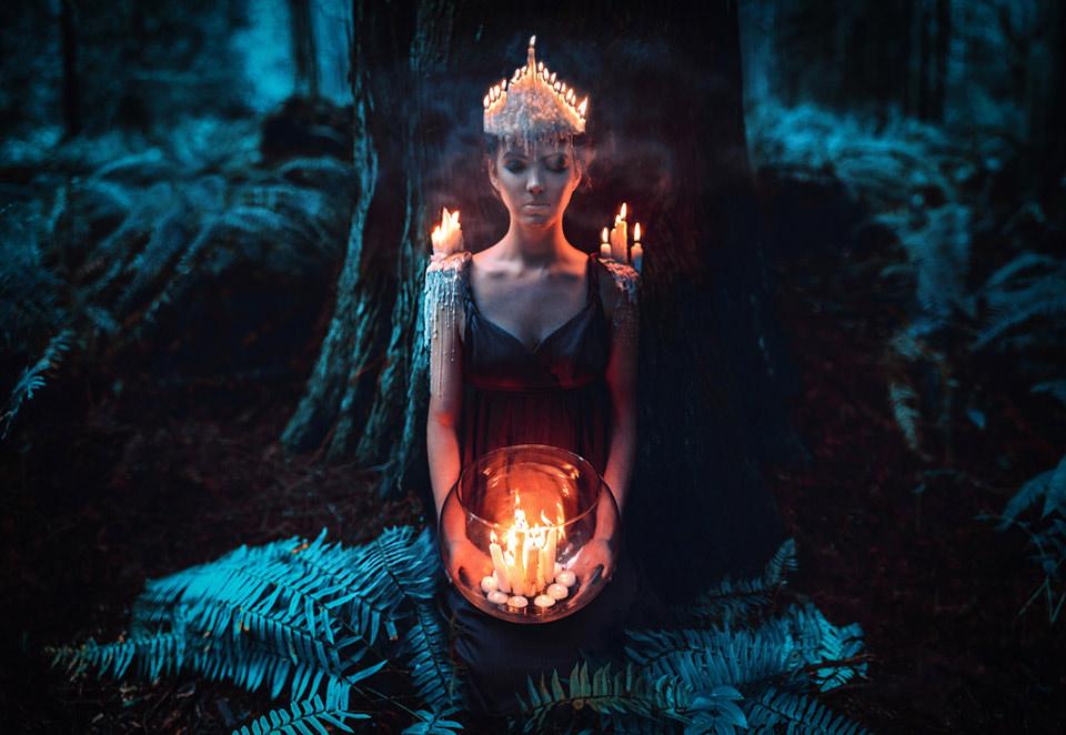 Eine Frau trät eine Krone aus brennenden Kerzen. Auf Schultern und Händen stehen ebenfalls Kerzen.