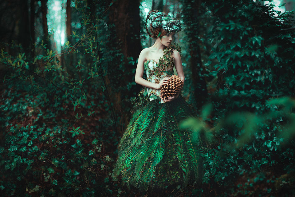 Eine Frau mit Efeukleid steht im Wald. Auf dem Kopf trägt sie Tannenzapfen.