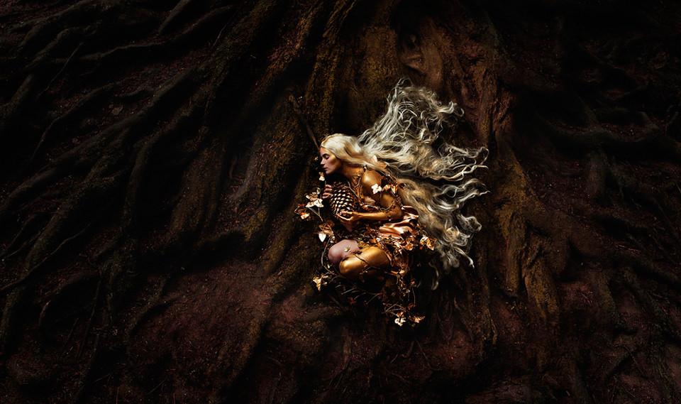 Eine goldene Frau hockt zwischen Wurzeln.
