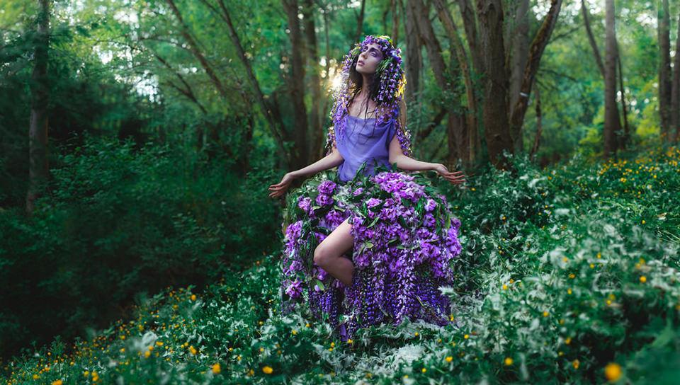 Eine Frau trägt ein kleid aus violetten Blumen.