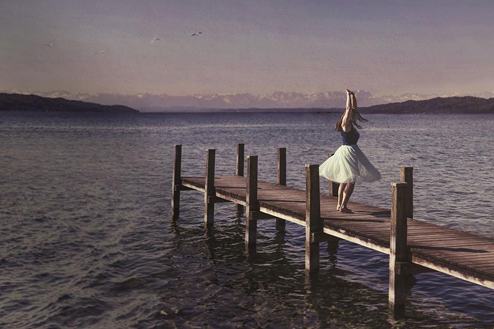 Eine Frau tanzt auf einem Steg über dem Wasser.