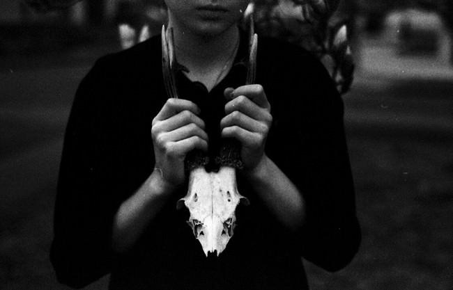 Eine Frau hält einen Tierschädel vor ihre Brust.