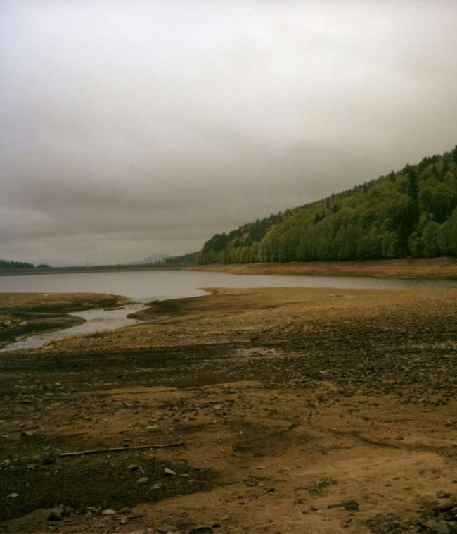 See mit einem kahlen Ufer, rechts im Hintergrund ein Wald.