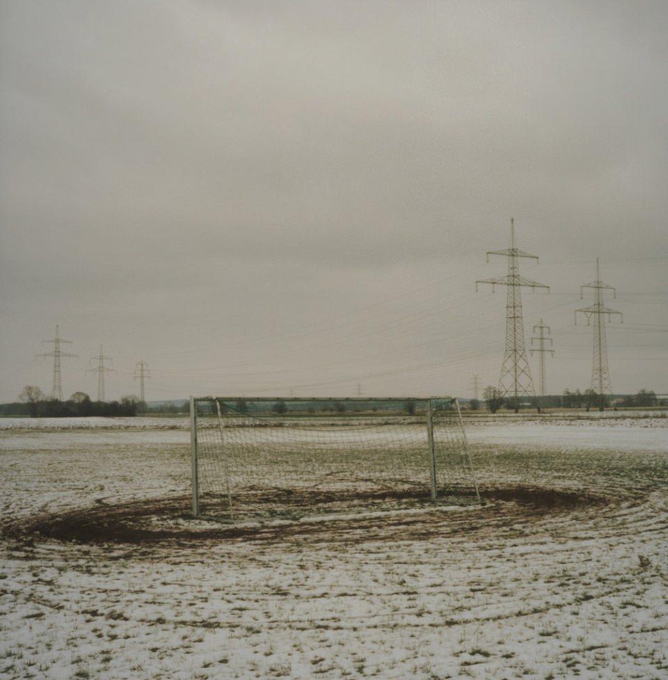 Ein schneebedecktes Feld, auf dem ein Fußballtor steht.