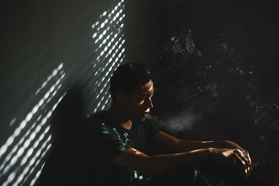 Ein Mann sitzt in einer sonnenbeschienenen Ecke und raucht. Der Rauch steigt dicht auf.