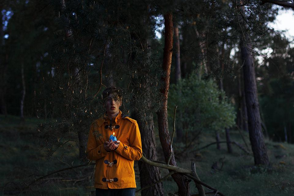 Ein Junge steht mit einer Kerze schützend unter einem Baum.