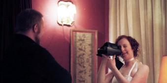 Eine Frau fotografiert einen Mann mit einer Polaroid-Kamera.