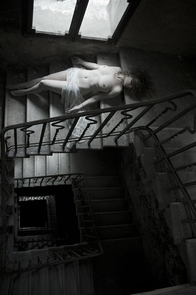 Eine Frau liegt halbnackt in einem Treppenhaus auf der Treppe.