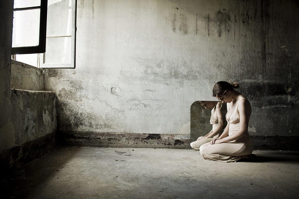 Eine Frau hockt in einem verlassenem Haus vor einem geöffneten Fenster.