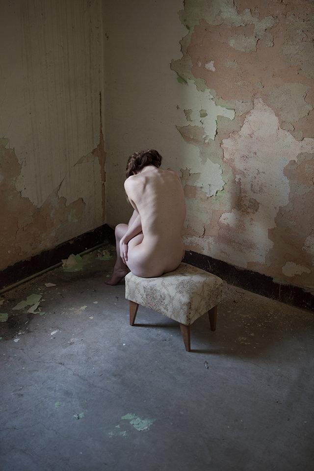 Eine Frau sitzt nackt auf einem Schemel in einer Zimmerecke.