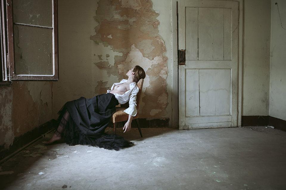 Eine Frau sitzt in einem verlassenem Haus auf einem Stuhl. Ihre Brüste sind entblößt.