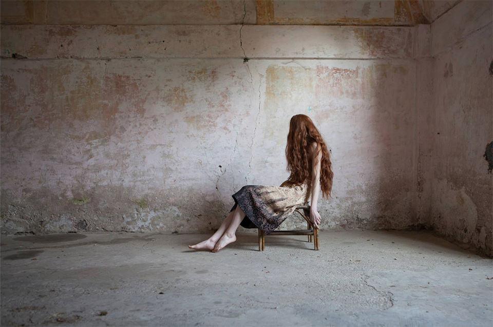 Eine Frau sitzt auf einem Stuhl. Ihre langen Haare fallen über ihr Gesicht.