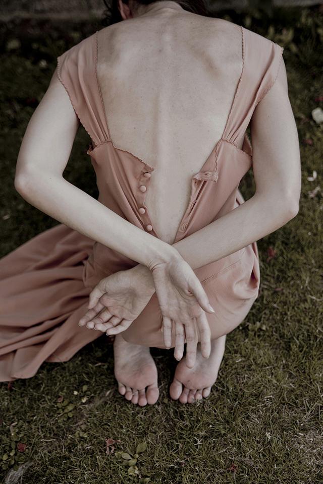 Eine Rückenansicht. Das Kleid der Frau ist geöffnet, sie hat die Arme hinter sich verschränkt.