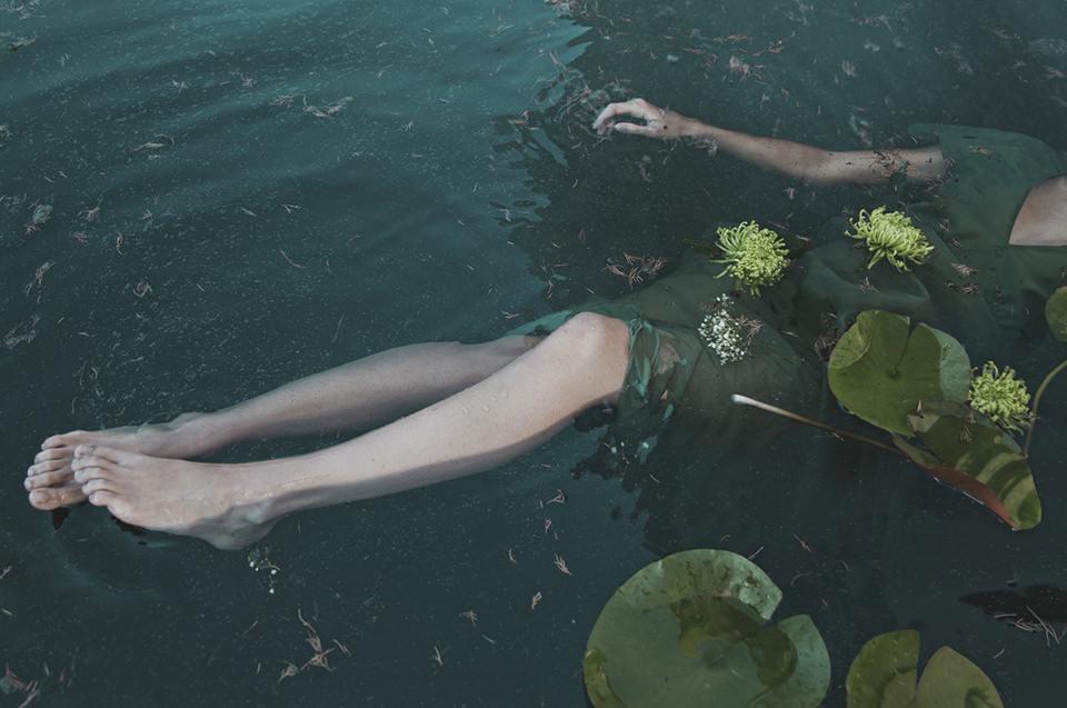 Eine Frau im Wasser von Seerosenblättern bedeckt.