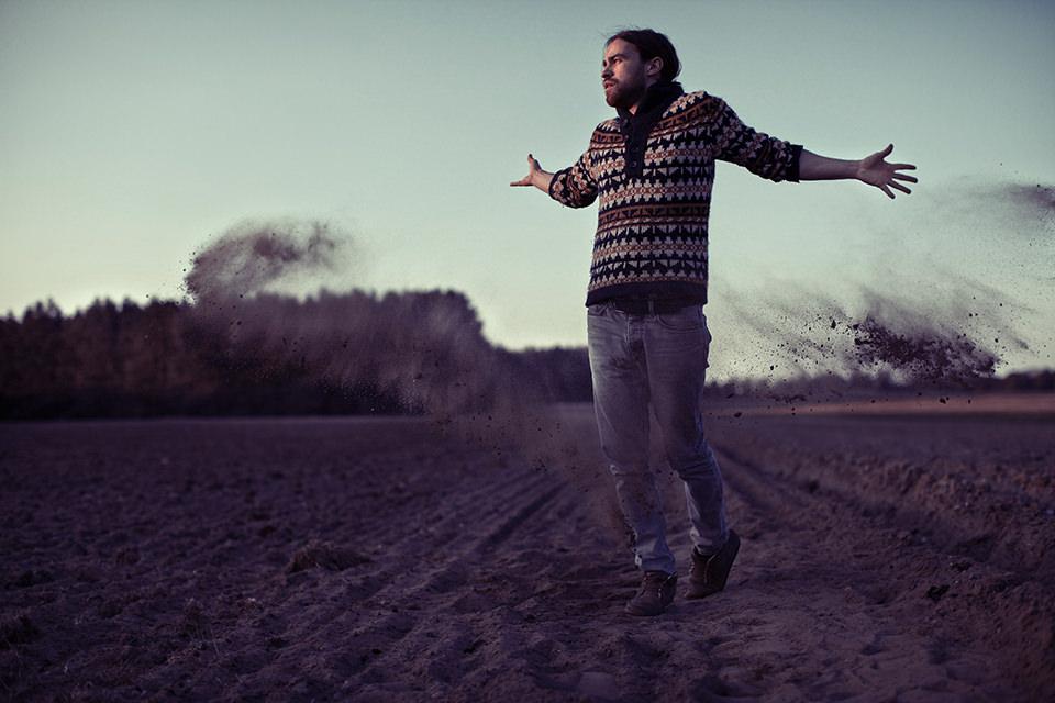 Ein Mann steht mit ausgebreiteten Armen auf einem Feld. Erde fliegt um ihn herum weg.