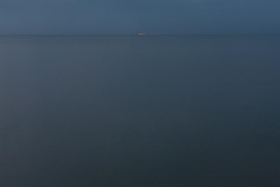 Ein weiter Blick über leeres Meer in der Dämmerung, am Horizont winzige Lichter.