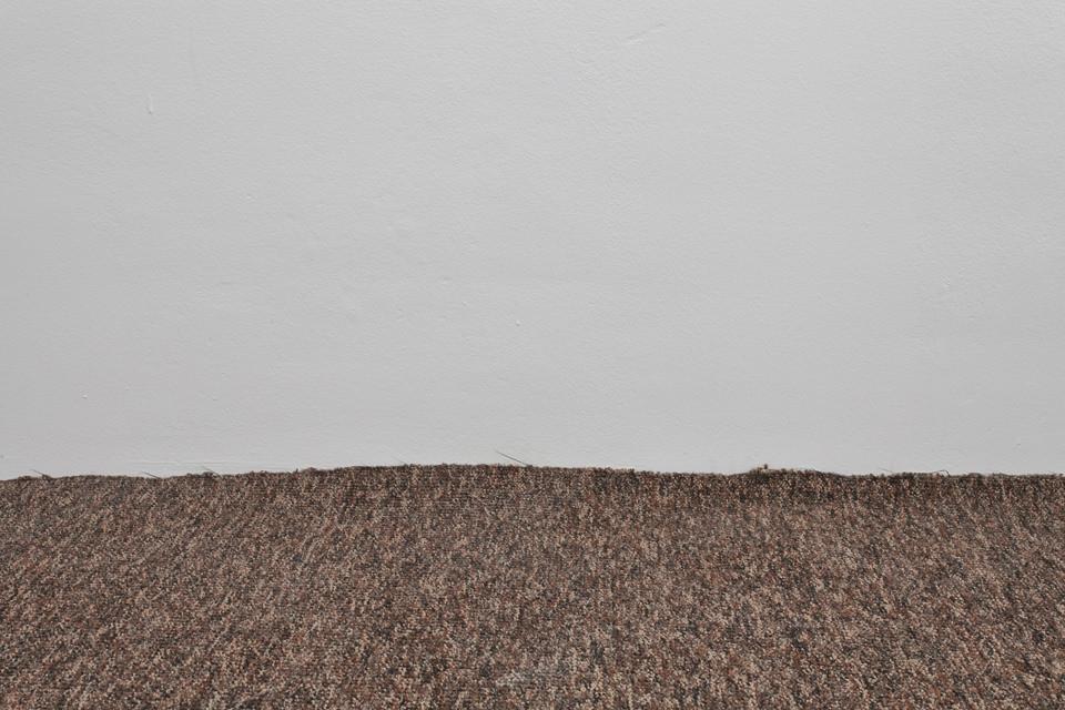 Ein Stück Teppich mit Hauswand.