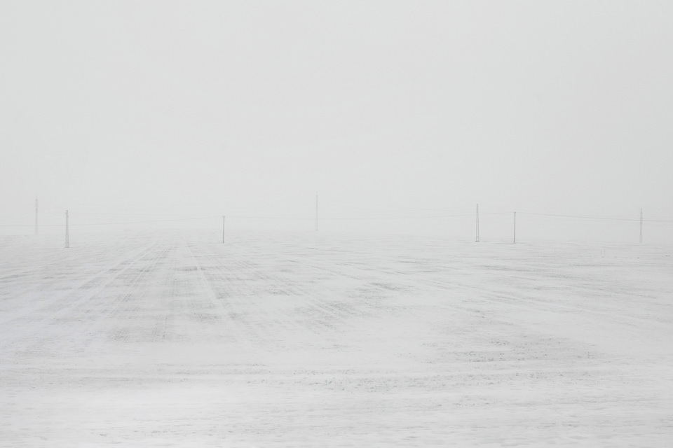 Ein weites schneebedecktes Feld mit Strommasten.