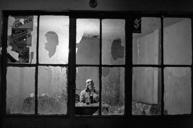 Ein Mann, gesehen durch kaputte Fensterscheiben.