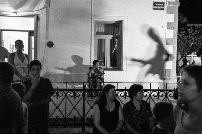 Menschen auf einer Veranstaltung, hinter denen ein Mann im Rollstuhl vor einer Wand sitzt, auf die Schatten von Musikern fallen.