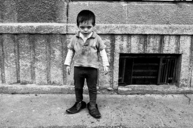 Ein kleiner Junge in viel zu großen Herrenschuhen.