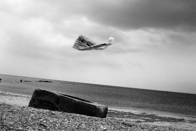 Am Strand fliegt eine Zeitungsseite über einem großen Stein.