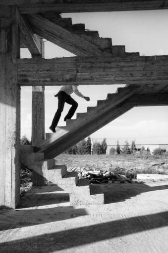 Ein Mann geht die Treppen eines Rohbaus hinauf.