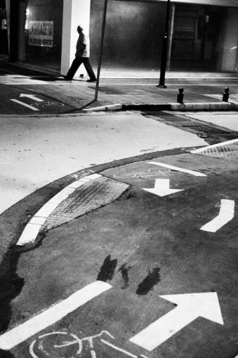 Eine Straße mit Markierungen, Pfeilen, Flecken und im Hintergrund ein Passant.