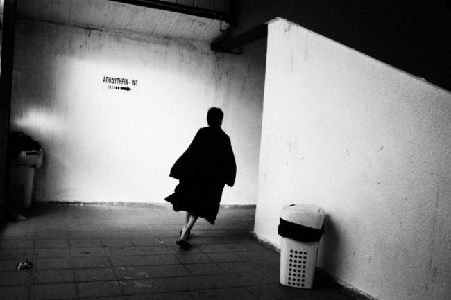 Eine Frau in dunklem Mantel biegt um die Ecke eines weißen Flurs.