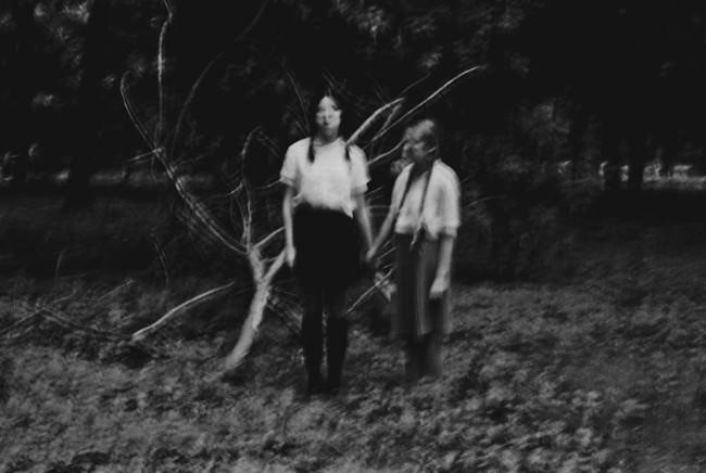 Zwei Mädchen halten sich an den Händen und stehen im Wald.
