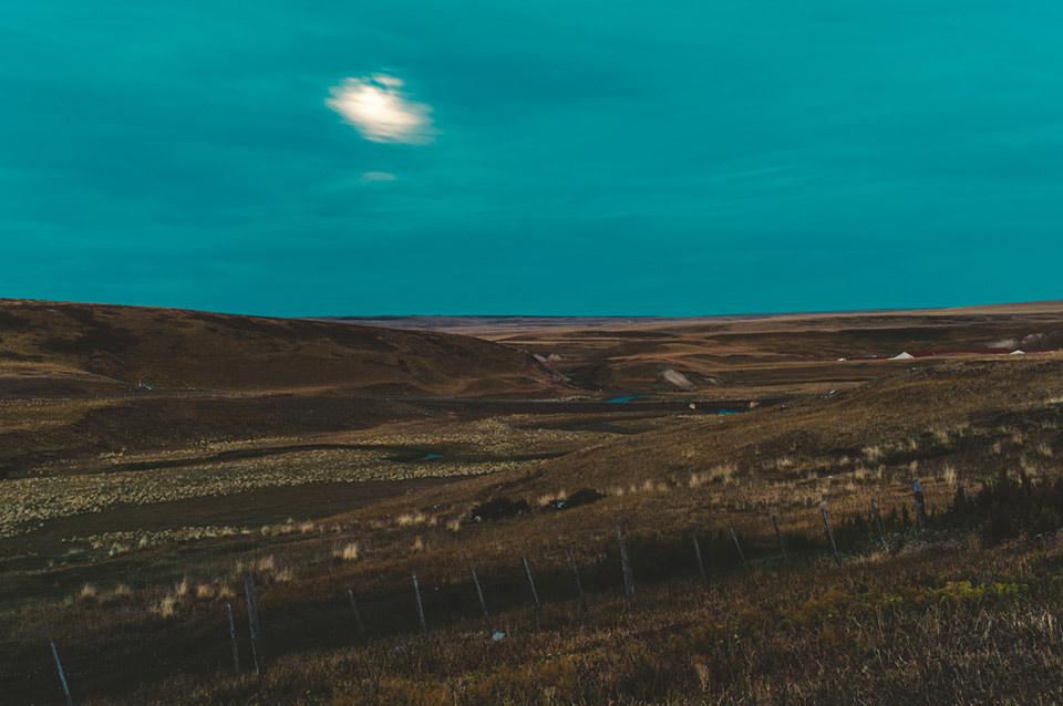 Eine düstere Landschaft. Zwischen den Wolken schimmert der Mond hindurch.