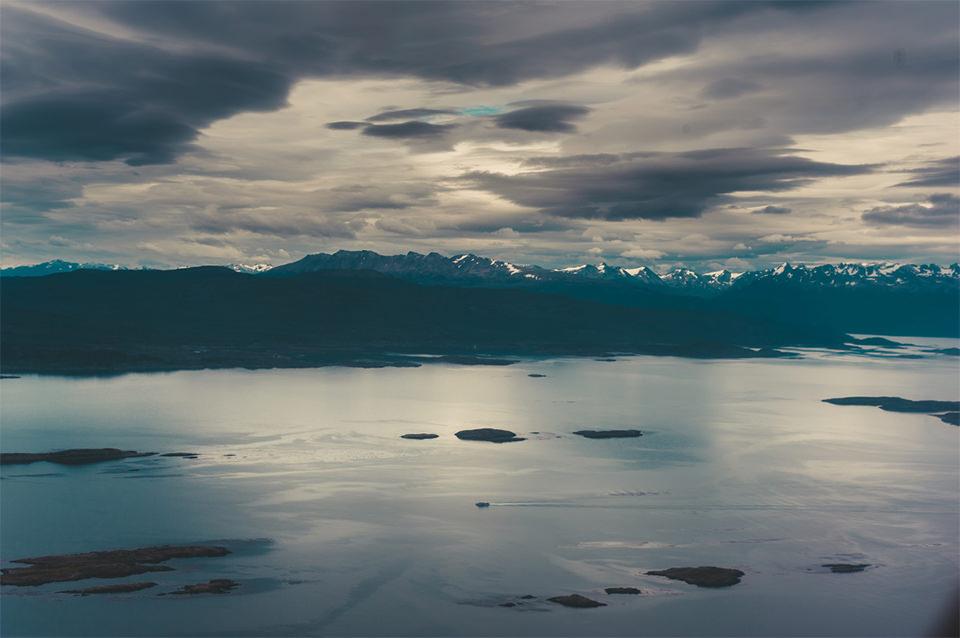 Im Vordergrund ein Meer, über dem am Horizont Berge zu sehen sind.