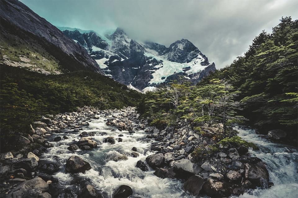 Ein Fluss im Vordergrund. Im Hintergrund ein eisbehangener Berg.