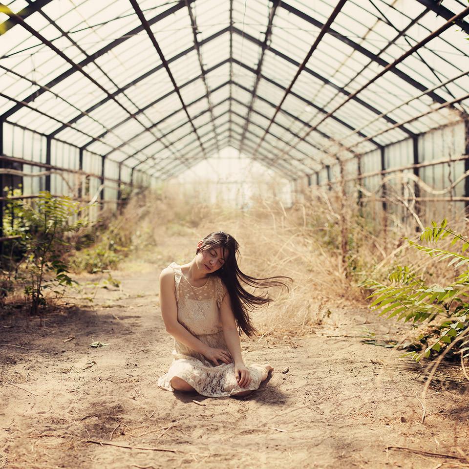Eine Frau sitzt in einem leeren Gewächshaus auf dem staubigen Boden.