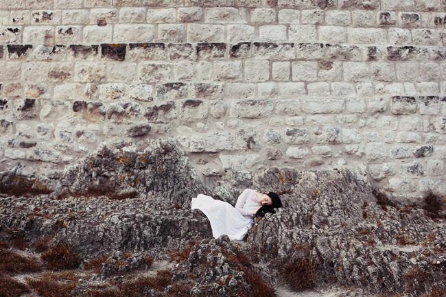 Eine Frau im weißen Kleid ruht auf Felsen vor einer alten Mauer.