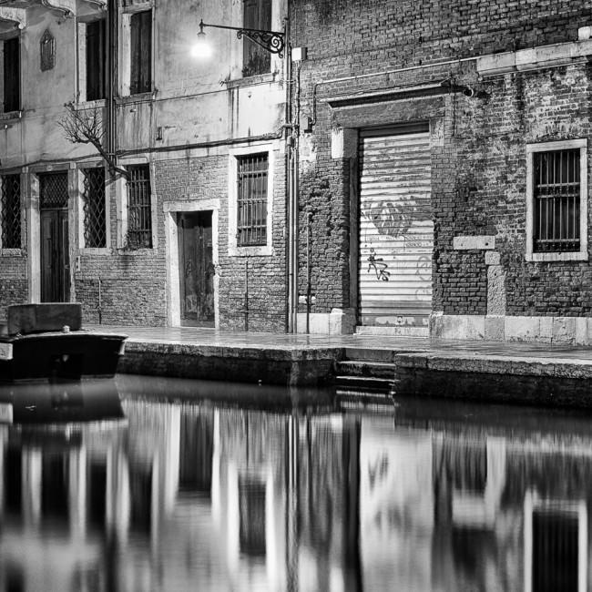 Eine Hausfassade in der Nacht, die sich im Wasser spiegelt.