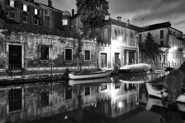 Gracht in der Nacht mit Laternenschein und Spiegelung im Wasser.
