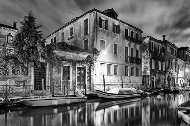 Gracht mit Haus, Laterne und Booten bei Nacht.