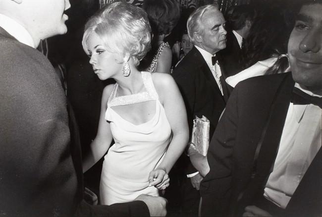 Eine Frau tanzt auf einer Party zwischen Männern.