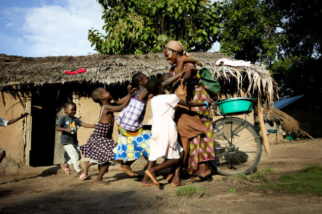 Eine Frau steht mit ihrem Fahrrad vor einer Hütte, wo eine Gruppe Kinder sie freudig umringt.