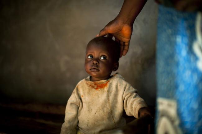 Ein Kleinkind in schumutziger Kleidung schaut zu einer Person hoch, die ihre Hand an den Hinterkopf des Kindes hält.