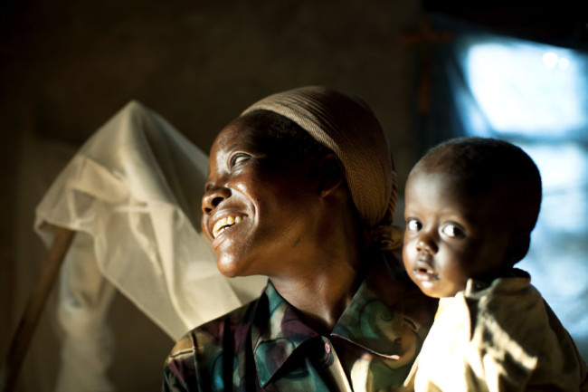 Eine lachende Frau hält ein Kleinkind auf dem Arm.
