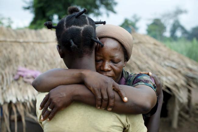 Eine Frau hält tröstend mit geschlossenen Augen eine andere Frau umarmt.