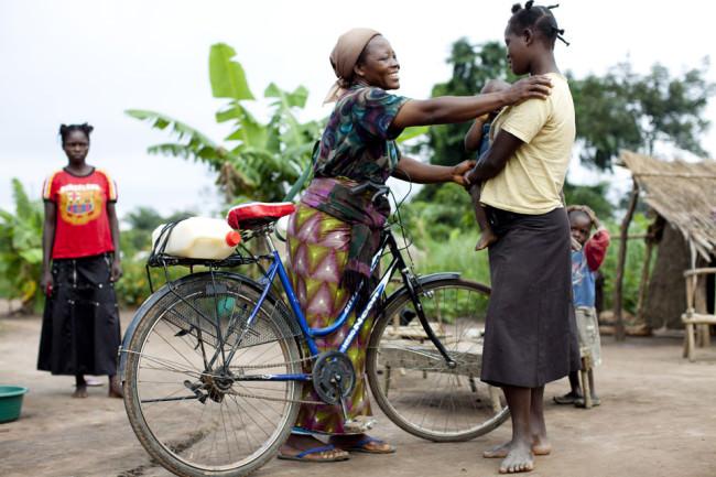 Eine Frau mit Fahrrad legt lachend einer zweiten Frau, die ein Kind auf dem Arm trägt, ihre Hand auf die Schulter.