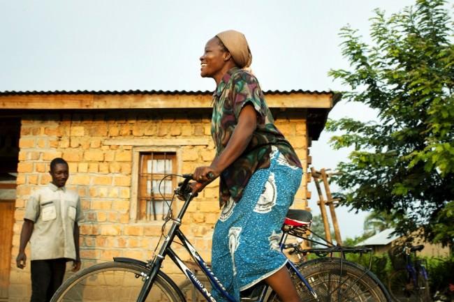 Eine Frau fährt auf einem Fahrrad vor einer Hütte.