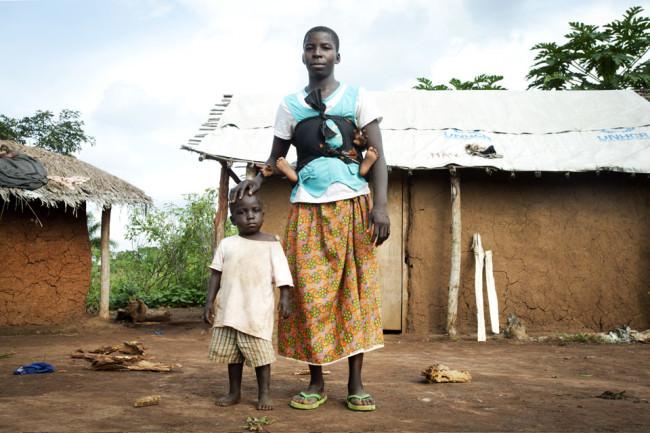 Eine Frau mit zwei Kindern posiert vor zwei Hütten.