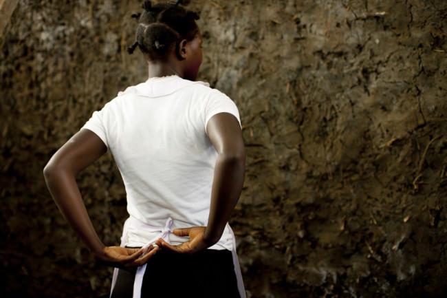 Eine Frau bindet ihre Schürze im Rücken.