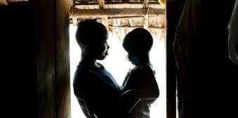 Eine Frau hält in einem Türrahmen ein Kind auf dem Arm. Sie stehen im grellen Gegenlicht, das von draußen in den dunklen Raum fällt.