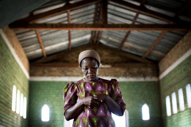 Eine betende Frau in einer sonst leeren, einfachen Kirche.