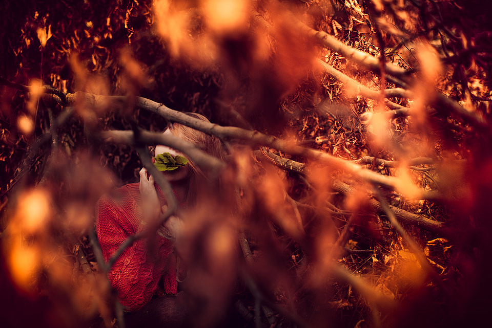 Eine Frau, versteckt hinter braunem Laub, trägt im Mund grüne Blätter.
